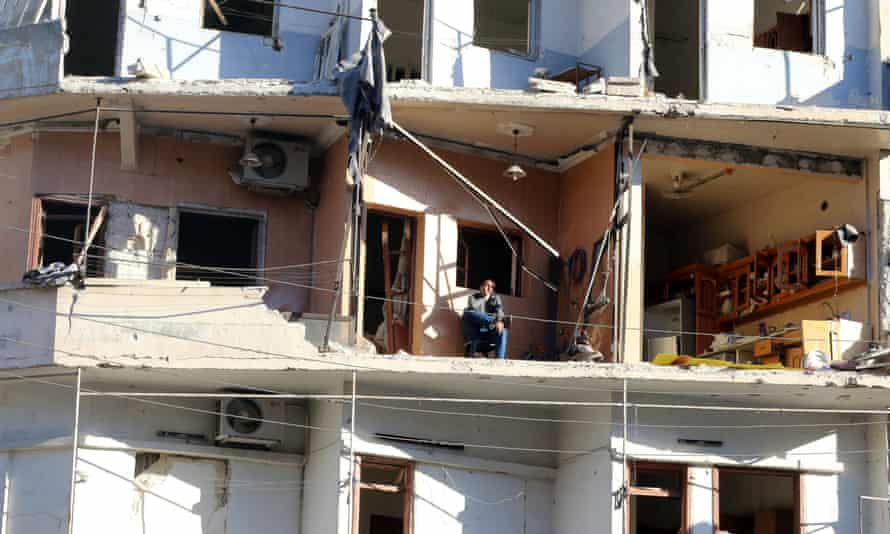 A man sits on the balcony of his damaged house in the rebel held besieged al-Sukkari neighbourhood of Aleppo.
