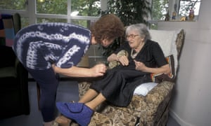 A woman tending to an elderly lady in a care home