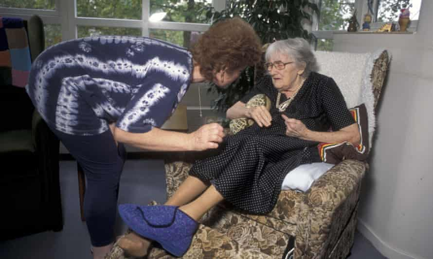 An elderly woman receives help in a care home