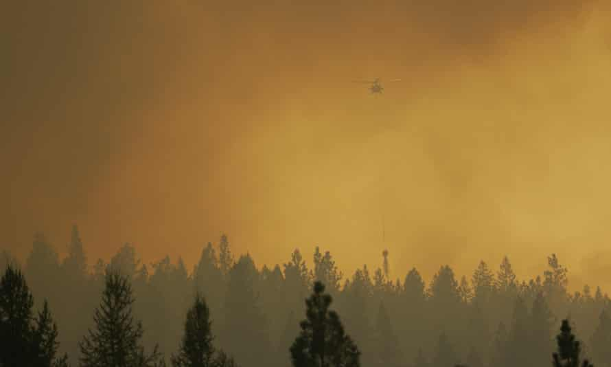 A helicopter makes a water bucket drop in Washington during a summer marked by wildfires in the western US, that is set to be the country's 12-hottest.