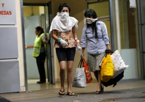 People cover their faces while leaving hospital Cosme Argerich, after the first fatality from coronavirus in Latin America was confirmed in Buenos Aires.