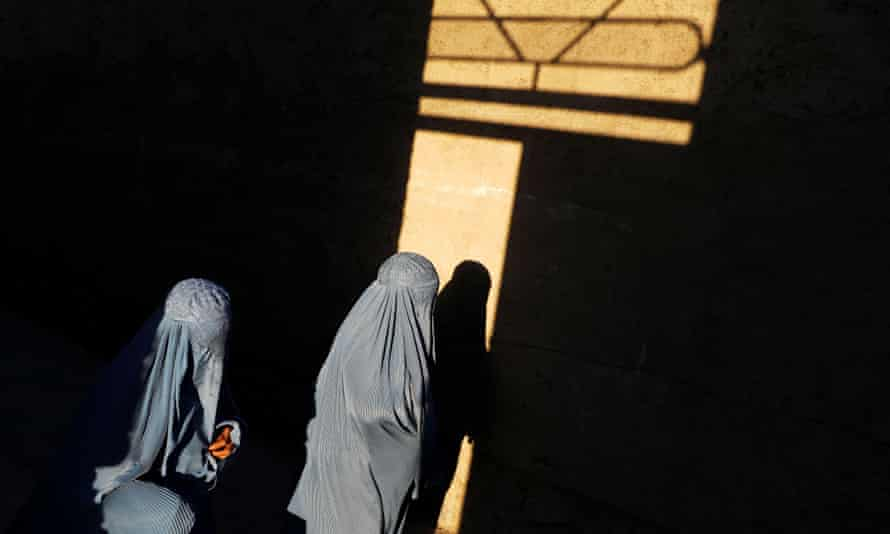 Two women in grey burqas illuinated in a shaft of yellow sunlight through a window, shining on a wall,  in an otherwise dark place
