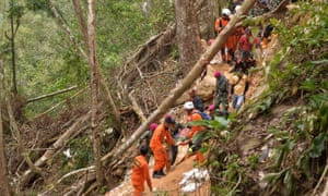 Members of an Indonesian search and rescue team carry a survivor after a mine collapsed in Bolaang Mongondow
