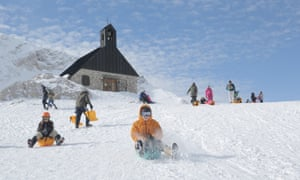 Children sledging down Zugspitze top, Bavaria.