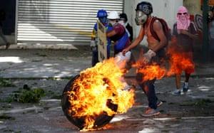 Demonstrators burn tyres to block streets at an anti-Maduro rally.