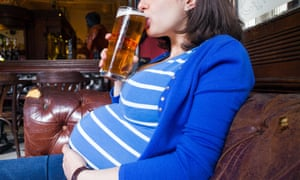 Pregnant woman drinking a pint of beer