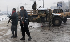 Afghan security force members guard the scene of a suicide attack that targeted the entrance gate of Marshal Fahim military academy in Kabul, Afghanistan on Tuesday.