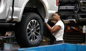 A Ford Motor Company worker works on a Ford F150 truck on the assembly line at the Dearborn Truck Plant