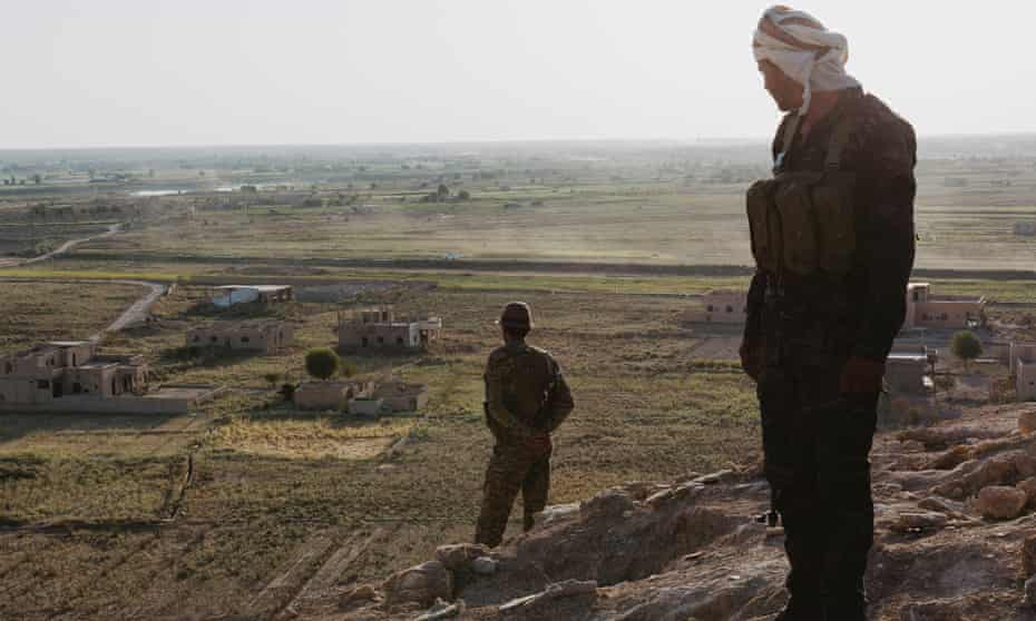 Kurdish soldiers stand guard on a hill overlooking the Euphrates river, near the border with Iraq.
