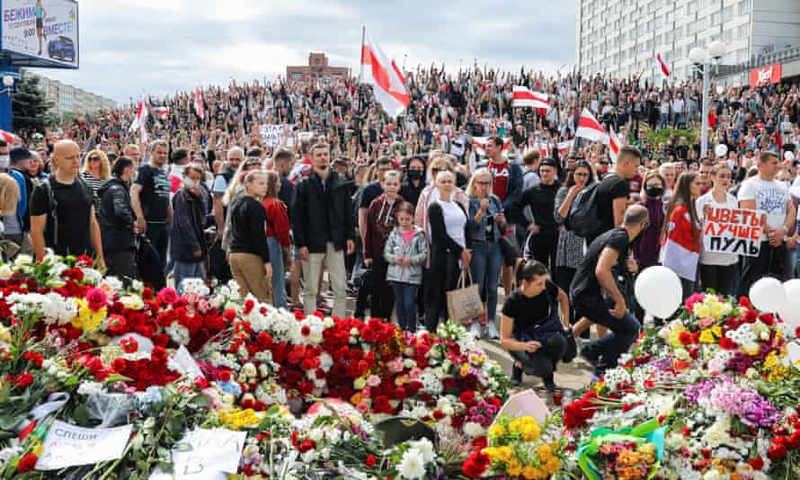 A large crowd of people holding signs in front of a large display of memorial flowers.