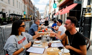 """Diners enjoy their drinks as they sit at tables outside a restaurant in London on August 3, 2020, as the Government's """"Eat out to Help out"""" coronavirus scheme to get consumers spending again gets underway."""