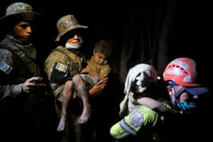 A soldier carries a rescued child covered with ash in El Rodeo