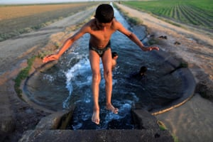 Raqqa, Syria   A boy cools off in an irrigation canal on the outskirts of Raqqa in Syria