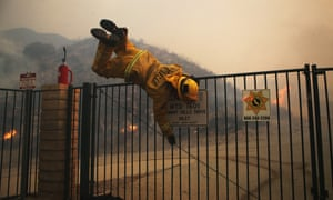 A firefighter hops over a locked gate while working the Tick fire on 24 October 2019.