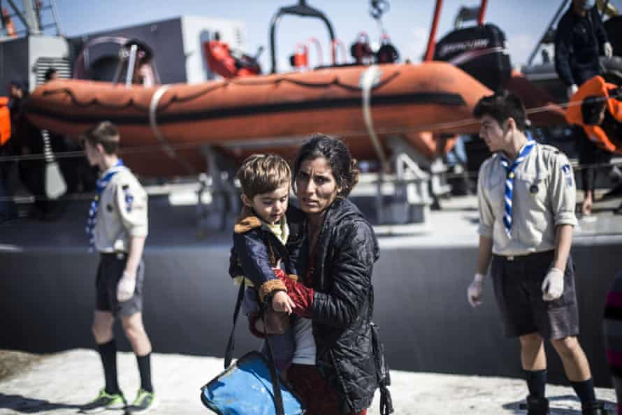 A Syrian Kurdish woman holds her son at the port of Mytilene.