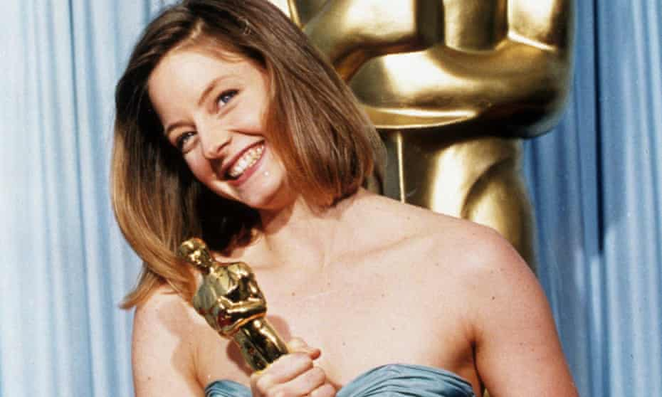 Jodie Foster, smiling, holding her Oscar at the Golden Globes in 1989