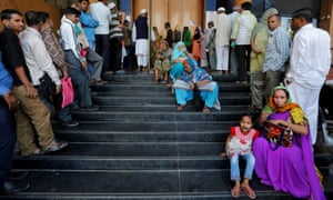 People in Ahmedabad wait for a bank to open so that they can withdraw and deposit money