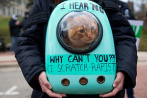 Ypsilanti, US. Goose, a nine-month-old cat, sits in a backpack as people gather during a Speak Out Against Sexual Violence demonstration at Eastern Michigan University in Michigan