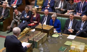 Theresa May reacts as Jeremy Corbyn speaks during PMQs