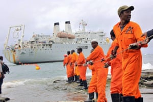 Workers haul part of a fibre optic cable onto shore, Mombasa