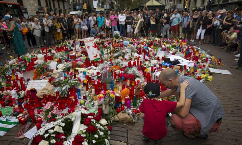 A man and his son light candles at a memorial tribute to the victims on Barcelona's historic Las Ramblas promenade on the Joan Miró mosaic.