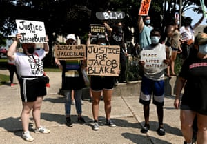 People hold placards as they gather for a protest outside the Kenosha County Courthouse yesterday