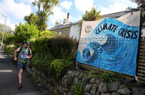 A runner passes a climate crisis banner in Carbis Bay