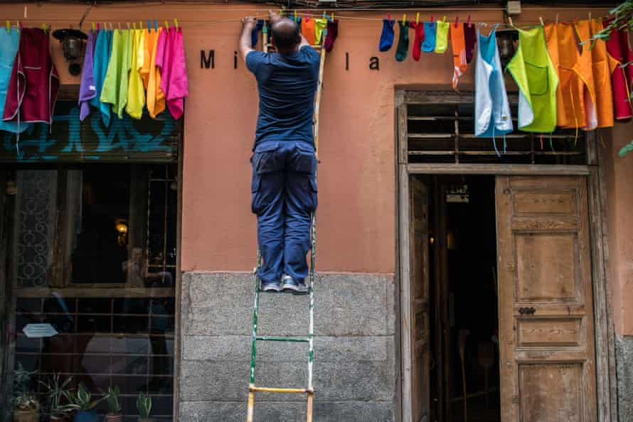 A man decorates his facade with clothes of the rainbow flag in Spain during the week of Pride celebrations.