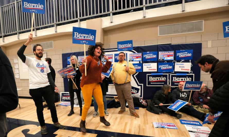 Supporters of Bernie Sanders hold signs at a caucus in Des Moines.