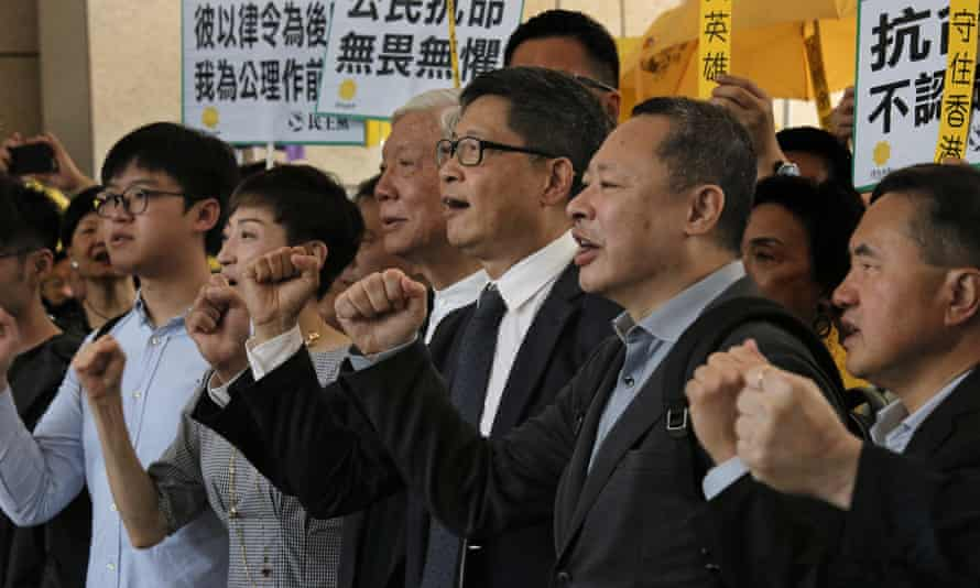 Occupy Central leaders, from right, Benny Tai, Chan Kin-man, Chu Yiu-ming, Tanya Chan and Eason Chung shout slogans before entering a court in Hong Kong.