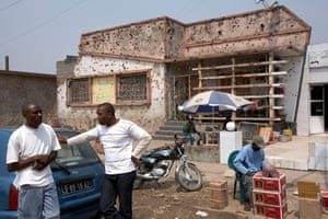 A street scene in Kuito, central Angola, 2007, with a bullet-ridden building showing the legacy of decades of conflict in the country, starting with the fight for independence from Portugal, followed by 25 years of civil war
