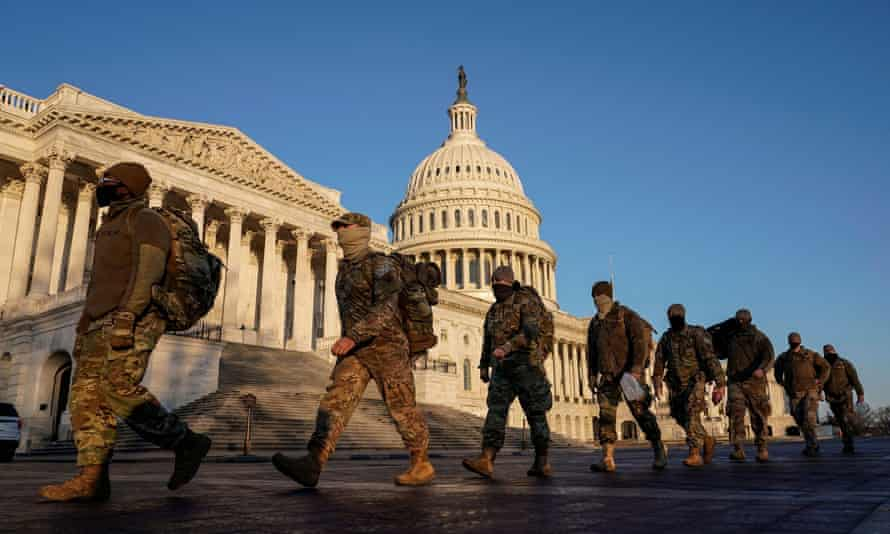 Members of the National Guard file past the US Capitol building in Washington DC.