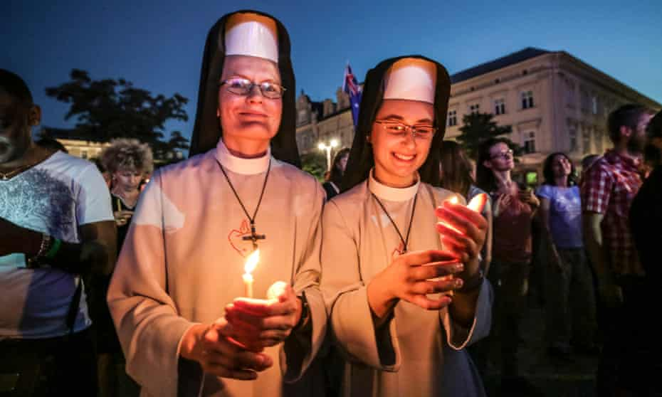 Two pilgrims hold candles at World Youth Day in Krakow, Poland