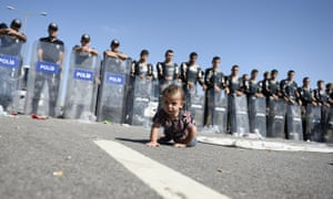 A baby crawls in front of Turkish police after refugees were stopped on their way into the city of Edirne.