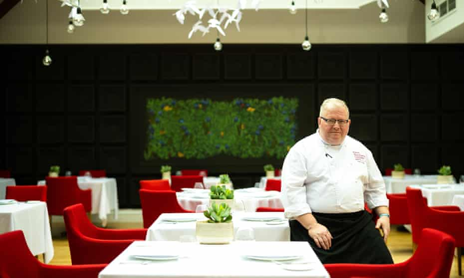 Paul Askew in chef's whites sitting to the right of the photograph by one of the geometrically arranged tables with white tablecloths and red chairs in his dining room