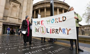 Liverpool central library. People hold a banner that reads the world in one library