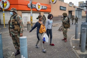 Residents returning from food shopping walk past national defence forces soldiers enforcing the coronavirus lockdown