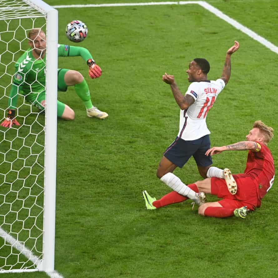 Simon Kjaer of Denmark scores an own goal for the England first goal whilst under pressure from Raheem Sterling of England.