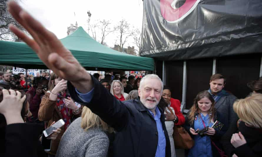 The Labour leader, Jeremy Corbyn, waves to supporters at the rally in support of the NHS in London.