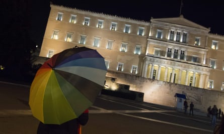 An activist with a rainbow umbrella outside the Greek parliament