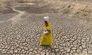 A woman carries an empty water pot as she crosses the dry bed of a pond at Mehmadpur village, 20km from Ahmedabad
