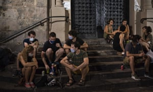 People sit in a public square in Barcelona