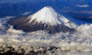 Snow-covered Mount Fuji, Japan's highest peak at 3,776-meter seen from an airplane window.