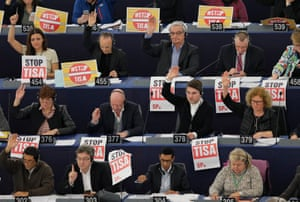Members of the Confederal Group of the European United Left hold posters with the slogan 'Stop Tisa' (Trade in Services Agreement) during a voting session at the European parliament in Strasbourg, France.