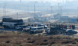 People wait next to vehicles as buses arrive at a Syrian government-controlled crossing on the outskirts of Aleppo