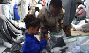 Children pack their cuddly toys in plastic bags as they disembark from a rescue ship in the port of Cagliari, Sardinia.