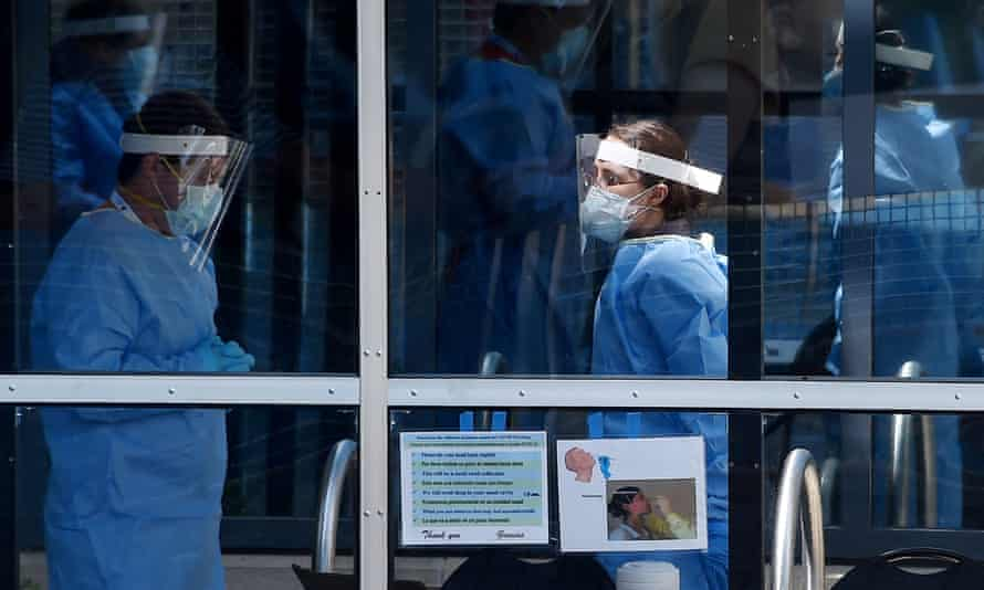 Healthcare workers wait for patients to be tested at a walk-in Covid-19 testing site on 12 May in Arlington, Virginia.