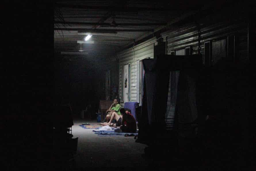Men sit under a battery-powered light