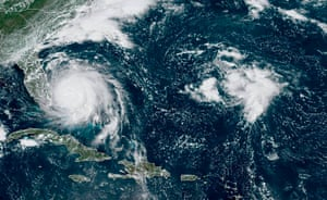 This GOES-16 satellite image taken Monday, Sept. 2, 2019, at 16:40 UTC and provided by National Oceanic and Atmospheric Administration (NOAA), shows Hurricane Dorian, left, churning over Bahamas. Hurricane Dorian hovered over the Bahamas on Monday, pummeling the islands with a fearsome Category 4 assault that forced even rescue crews to take shelter until the onslaught passes.