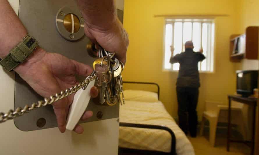 Guard unlocks a cell door.